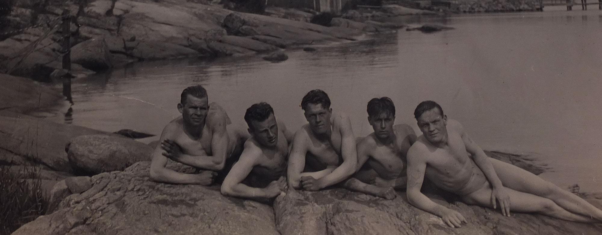 Fem nakna män som ligger på en klippa i skärgården.