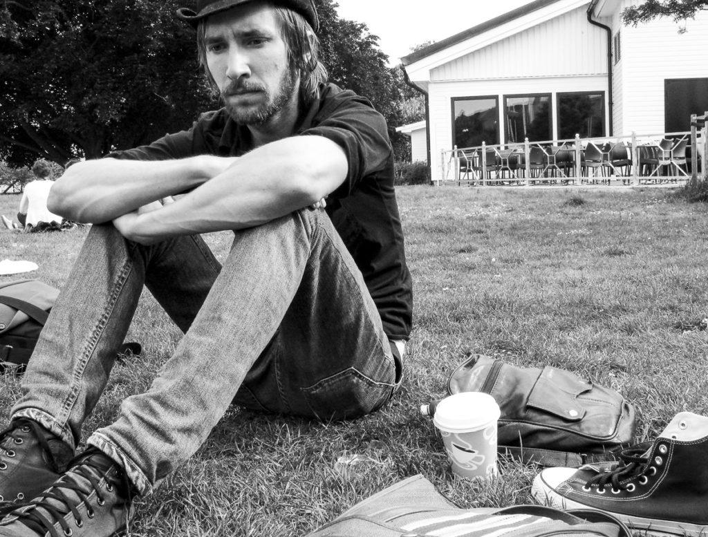 Pojke med hatt sittandes i en park